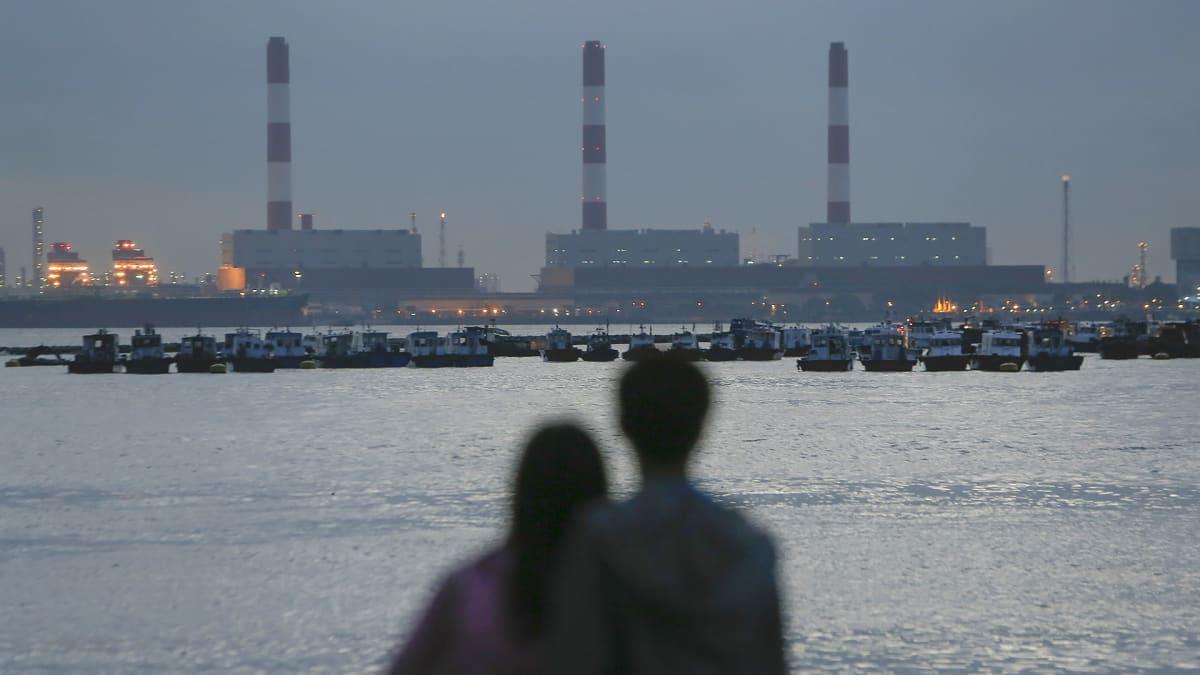 Pariskunta katselee iltavalaistua Jurongin saarta Singaporessa.