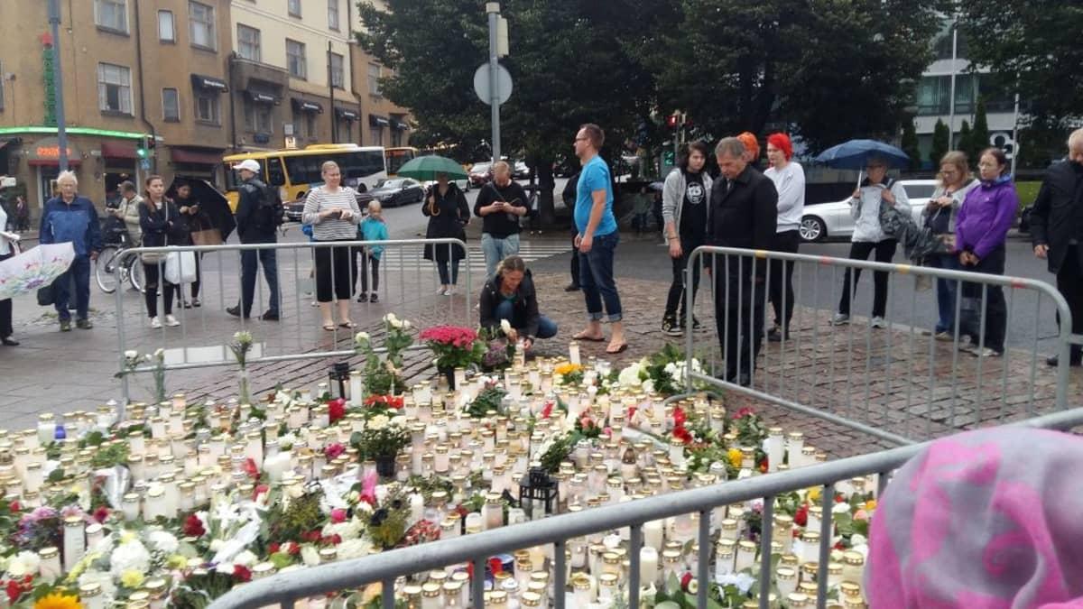 Tasavallan presidentti Sauli Niinistö laskee kukat Turun terroriteon uhrien muistoksi Turun Kauppatorilla.