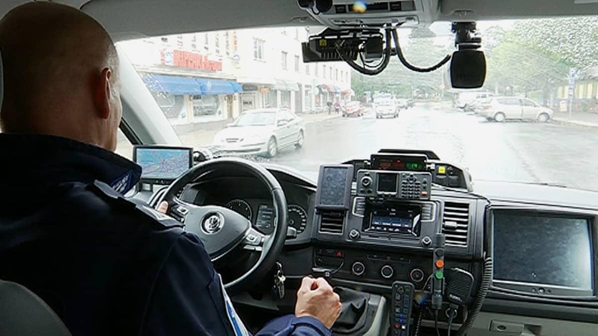 Poliisi ajaa poliisiautolla.