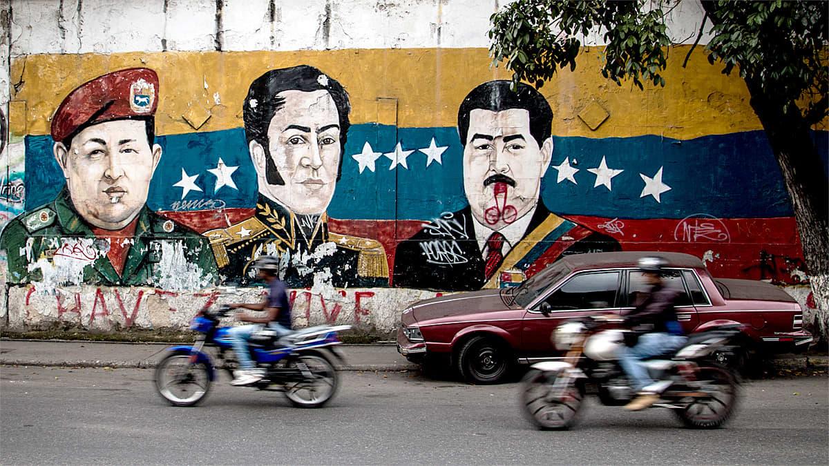 Katunäkymä, taustalla seinämaalaus kenraaleista ja presidentistä.