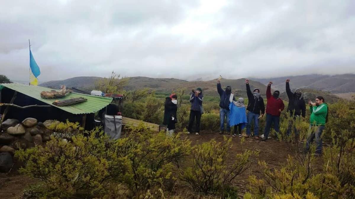 Aktivistit joilla suurimmalla osalla yksi käsi ylhäällä, sisovat vuoristoisessa maastossa. Vierellä peltikattoinen kivistä valmistettu asumus ja Mapuche-alkuperäiskansan lippu.