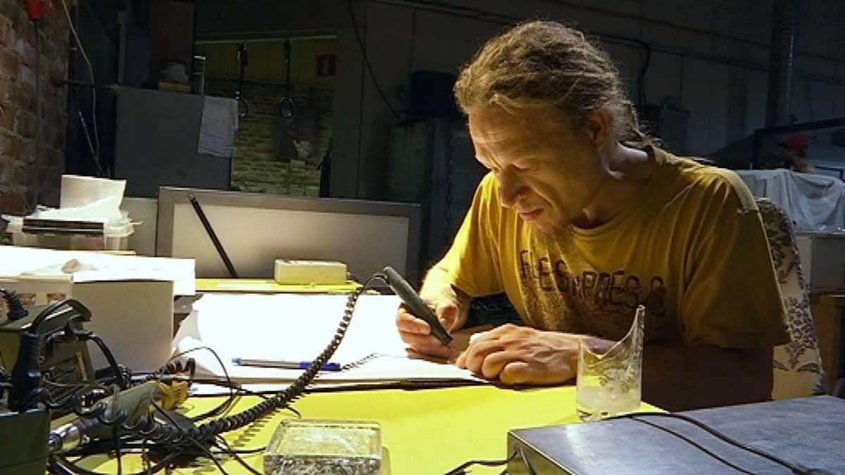 Mies työpöydän ääressä sähköisen kaivertajan kanssa