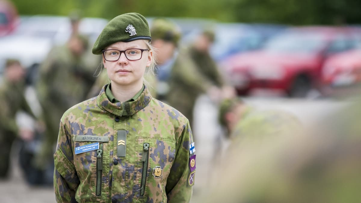 Naisten vapaaehtoista varusmiespalvelusta suorittava alikersantti seisoo ulkona harjoitusalueella.