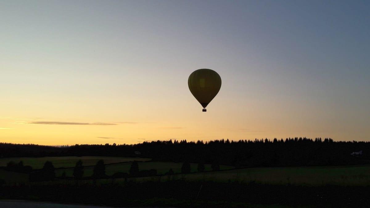 Kuumailmapallo lentää auringonlaskun maisemassa.