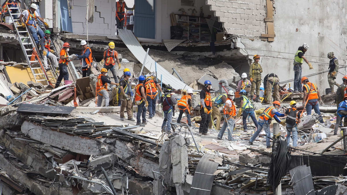 Raivaajia työssä toimistorakennuksen raunioilla.