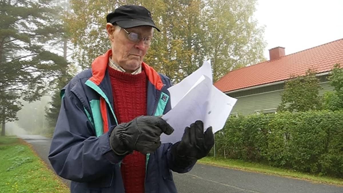 Silmälasipäinen vanhempi mies tutkiin papereitaan ulkona