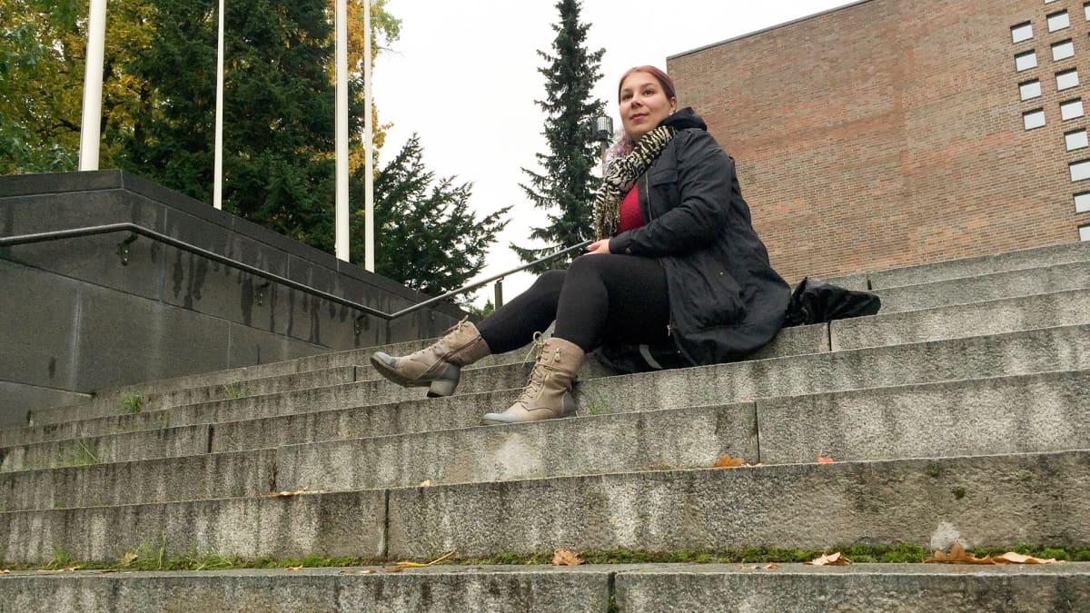 nainen istuu rappusilla