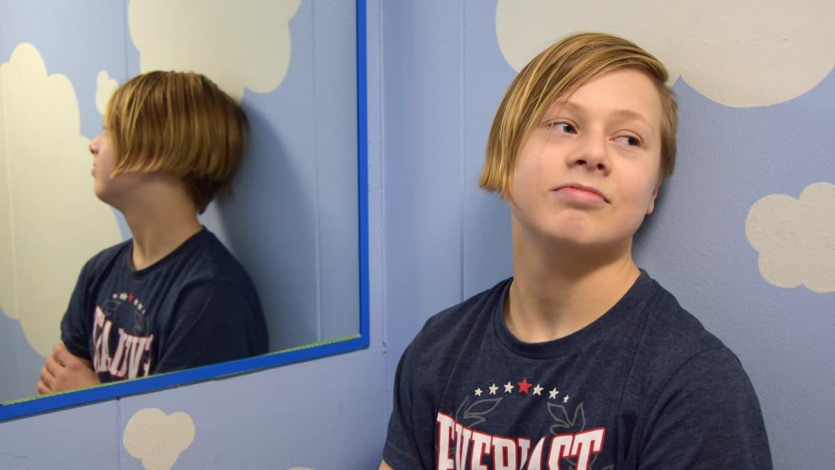 Poika katsoo poispäin kamerasta ja seisoo hississä.