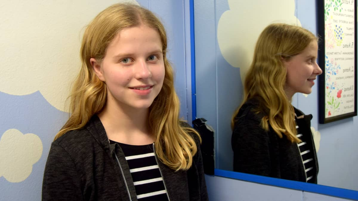 Tyttö seisoo hississä ja katsoo suoraan kameraan.