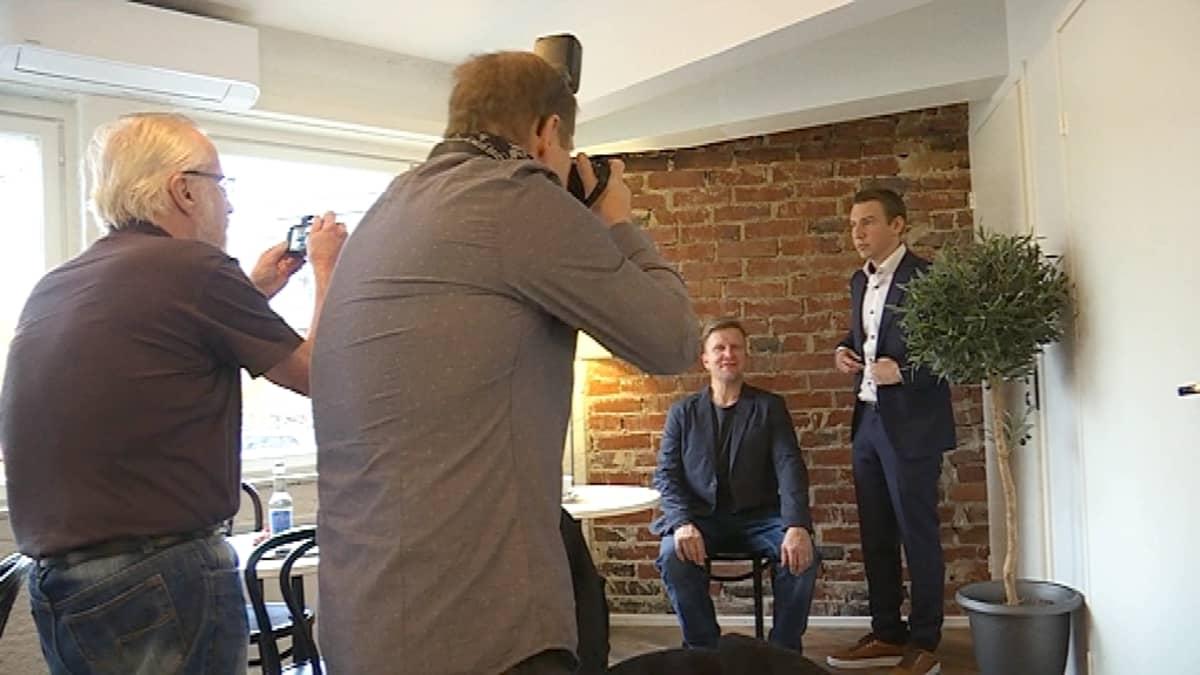 Kaksi miestä seisoo kahden muun miehen valokuvattavana