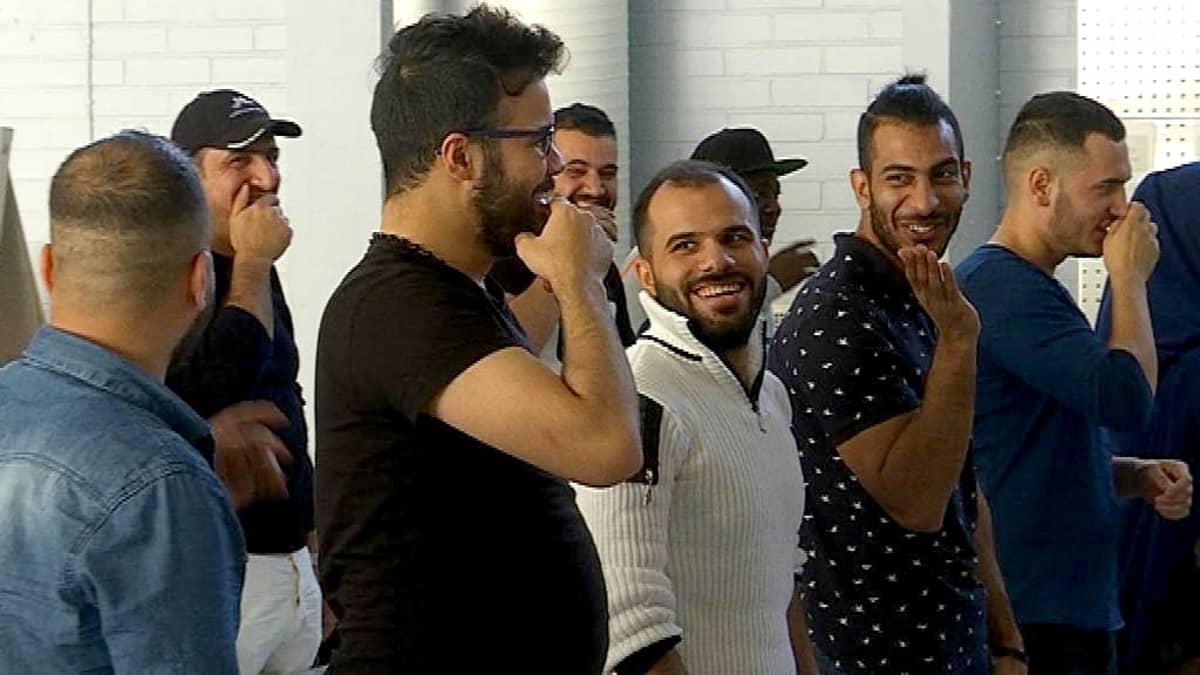 ulkomaalaiset miehet naureskelevat ja yrittävät laulaa suomenkielen sanoja