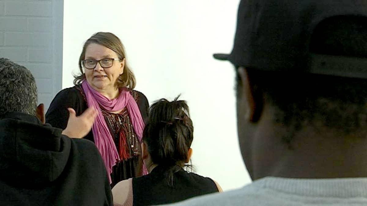 Silmälasipäinen nainen istuu opettjaan pöydän takana ja katselee oppilaitaan