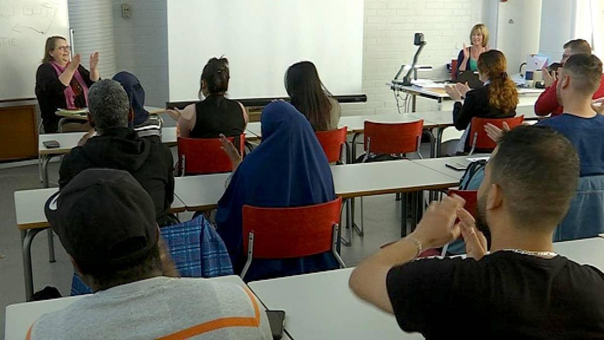maahanmuuttajia luokassa ja opettajat edessä taputtavat ryhmiä