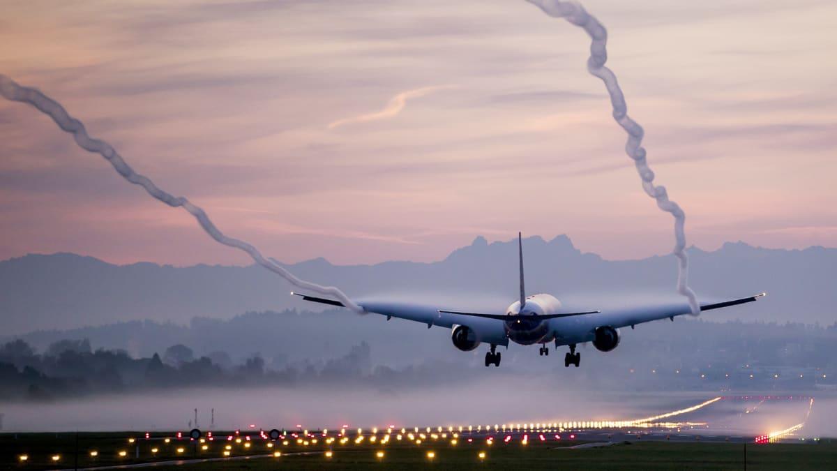 Lentokone laskeutuu illan hämärtyessä.