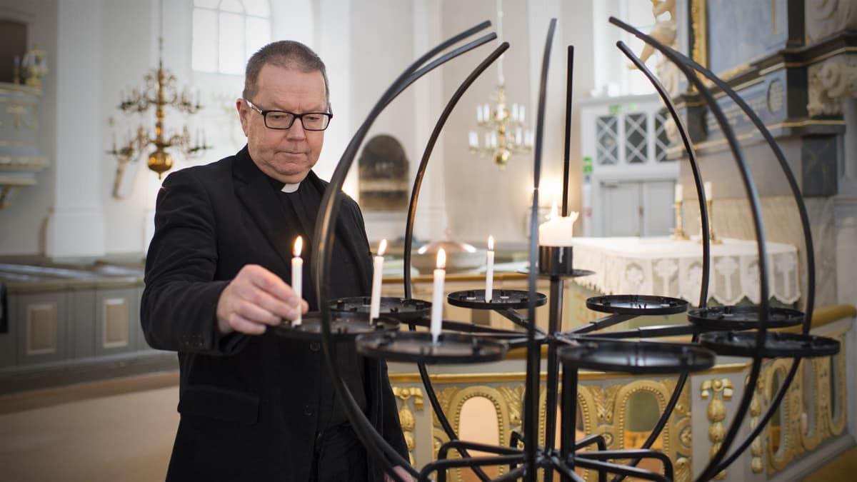 Kirkkoherra Hasse Häggblom sytyttää kynttilän.