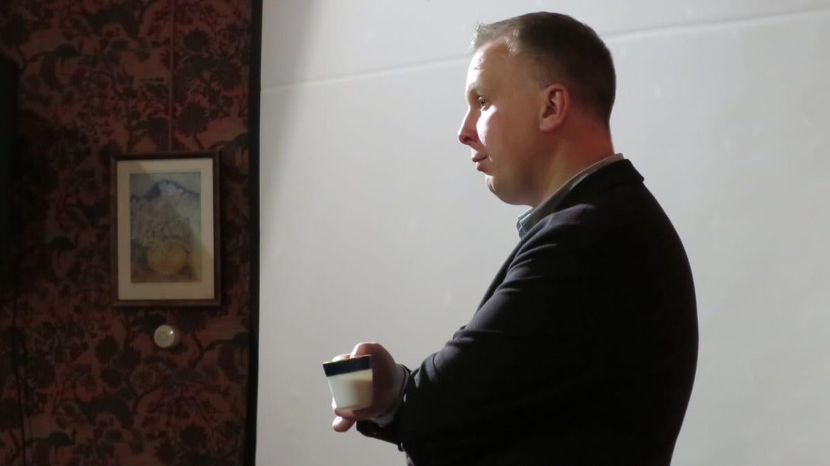 Mies seisoo ja pitelee kahvikuppia kädessään