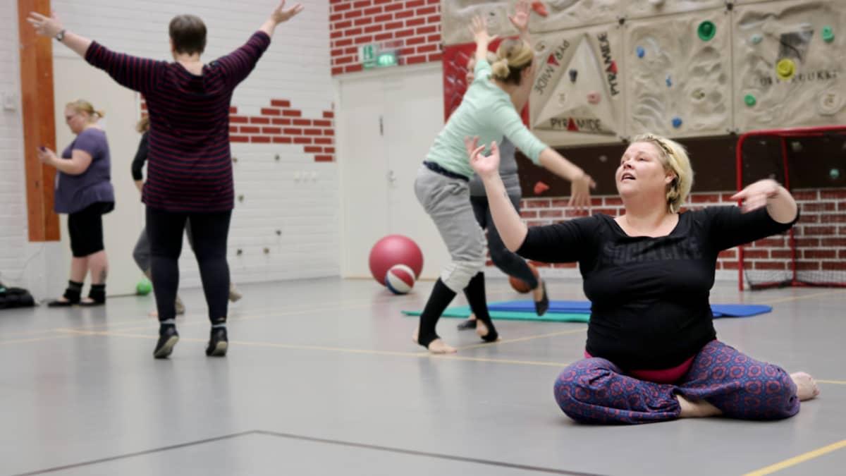 Naiset tanssivat liikuntasalissa