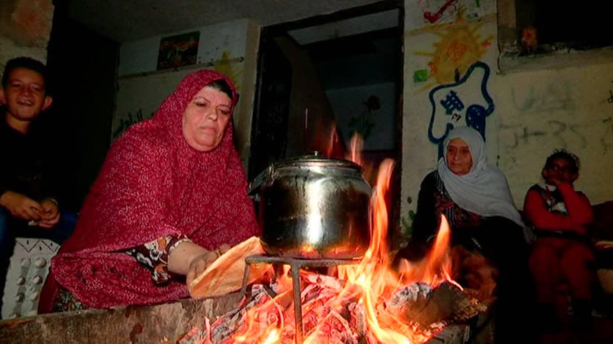Nainen lämmittää pataa tulella Gazassa.