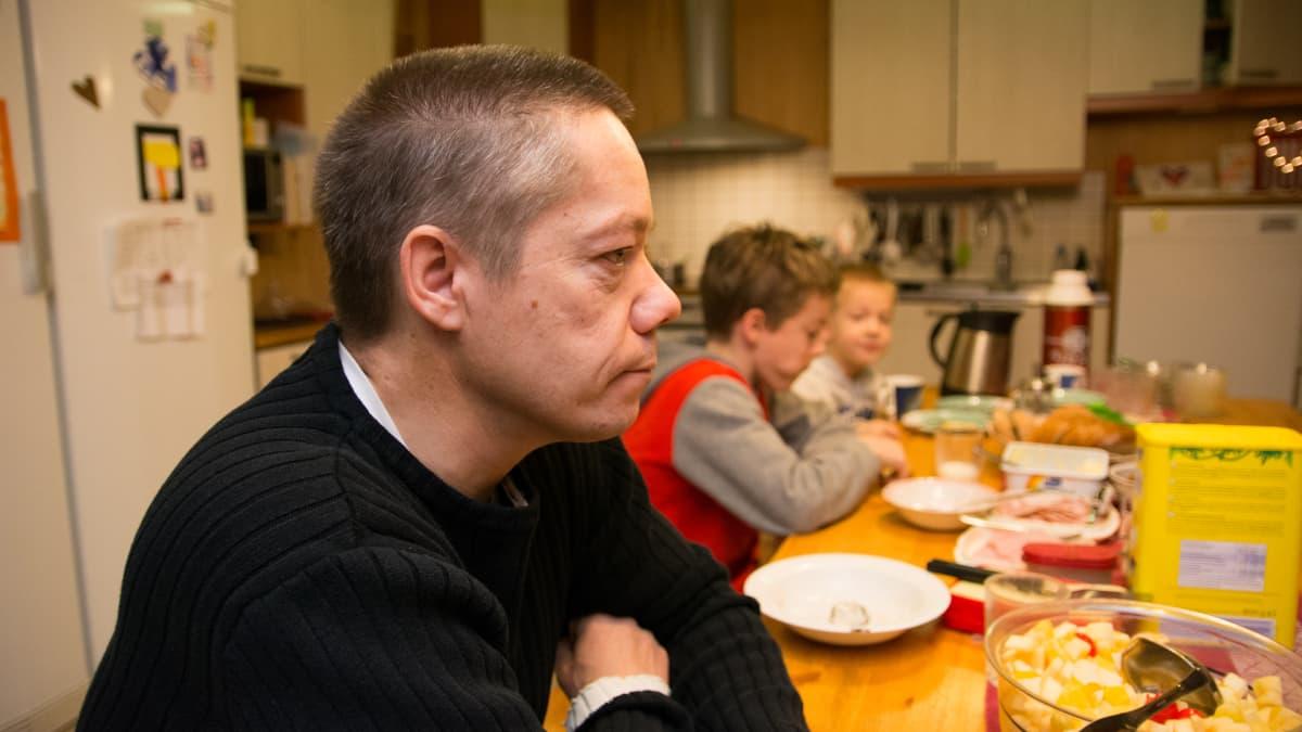 Isä istuu aamupalapöydässä kahden pienen pojan kanssa.
