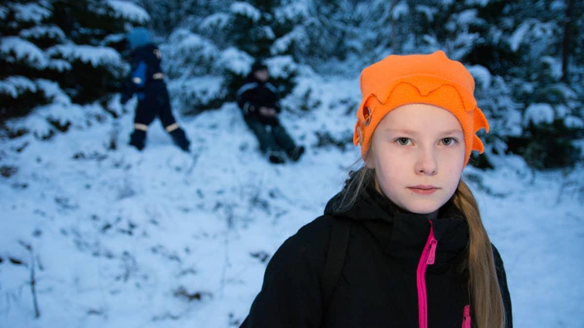 Tyttö ja kaksi poikaa talvisessa metsässä.