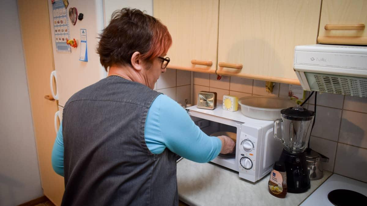 Lähihoitaja Birgit Latva laittaa puurolautasta mikroaaltouuniin.