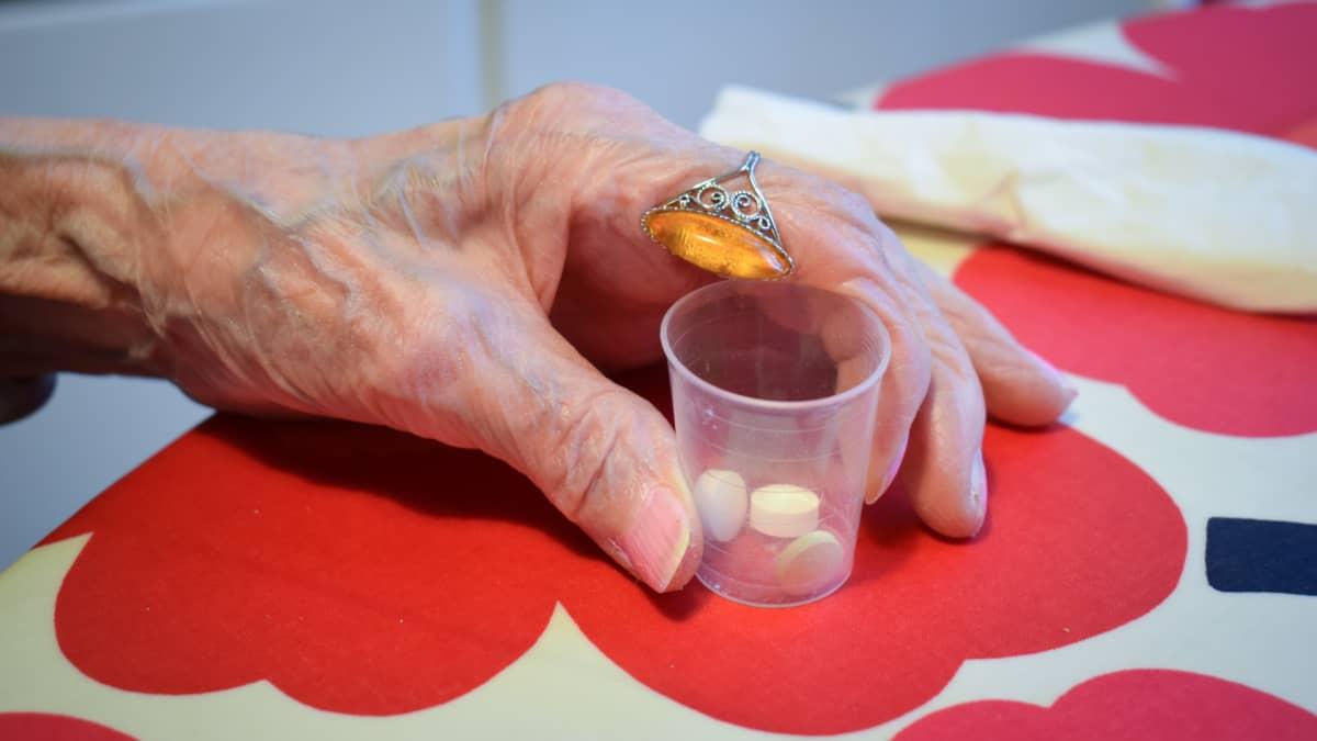 Lääkekuppi kädessä.