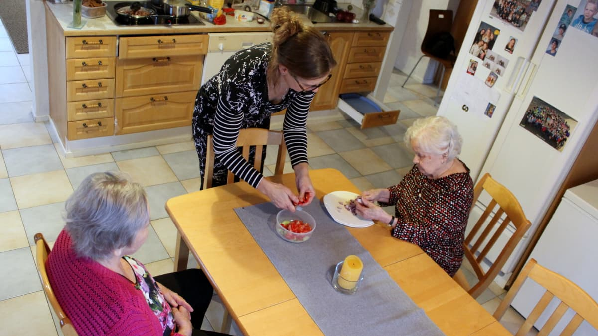 Kaksi ikäihmistä pilkkoo salaattitarpeita perhehoidossa keittiönpöydän äärellä.