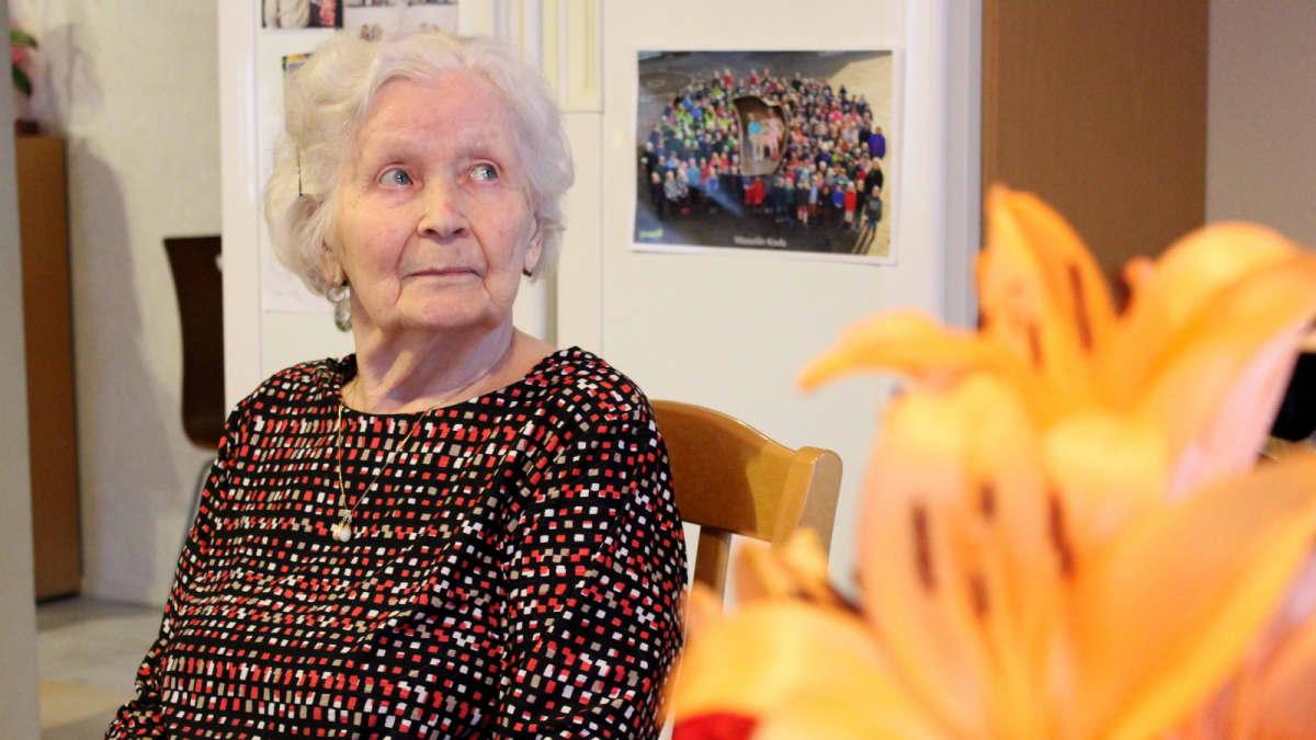 Vanhus istuu perhehoidossa keittiössä.