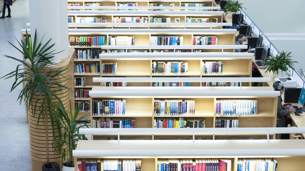 Jyväskylän kaupunginkirjaston kirjahyllyjä ja oikeassa reunassa näkyy myös tietokoneen käyttäjiä