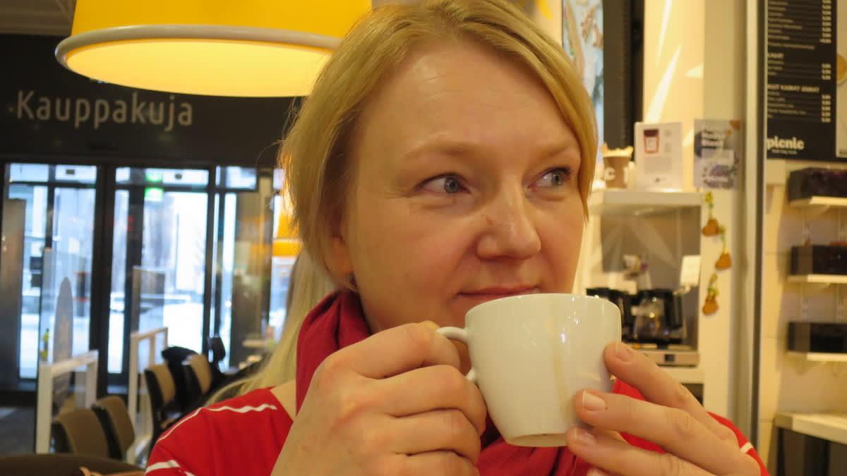 Vaalea nainen juomassa kahvia kahvilassa