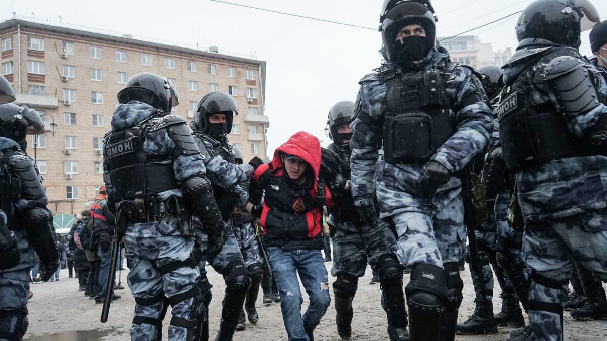 Poliisi kiinni ottamaa henkilö viedää poliisiautoon.