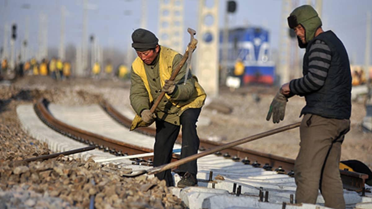 Kaksi siirtolaista kiinnittää rautatien kiskoja Shandongin maakunnassa joulukuussa vuonna 2009.