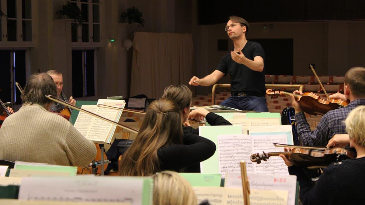 Pietari Inkinen johtaa orkesteria istualtaan.