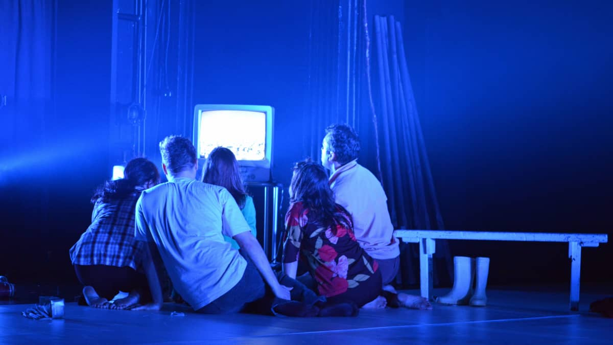 Esiintyjät katsovat näyttämöllä televisiosta elokuvaa Valkoisesta peurasta.