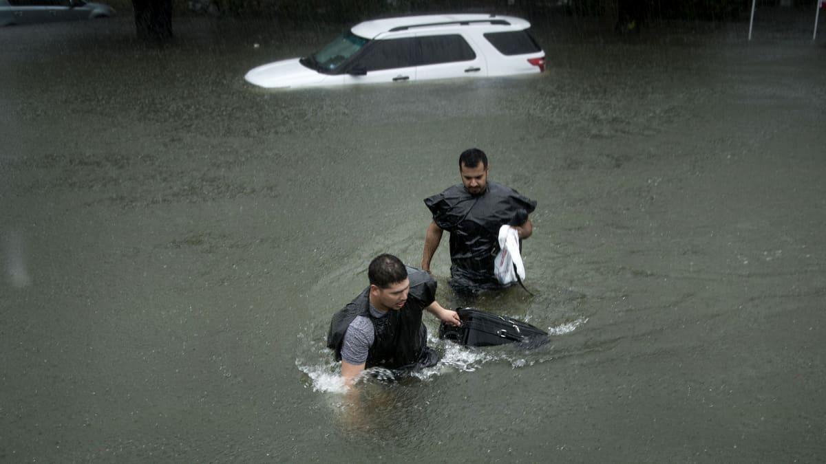 Tulva Galvestonissa jossa miehen ylittävät katua jossa on vettä heidän vyötäröönsä asti.