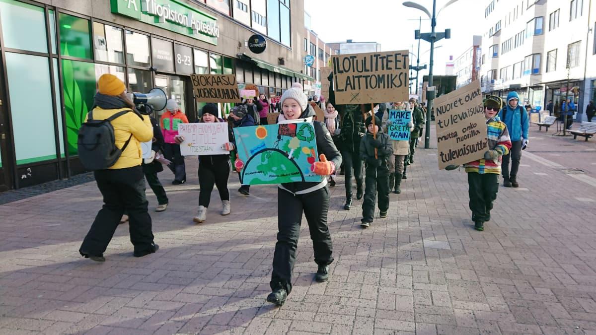 Joukko nuoria osoittaa Joensuun keskustassa mieltään ilmastonmuutoksen hillitsemiseksi.