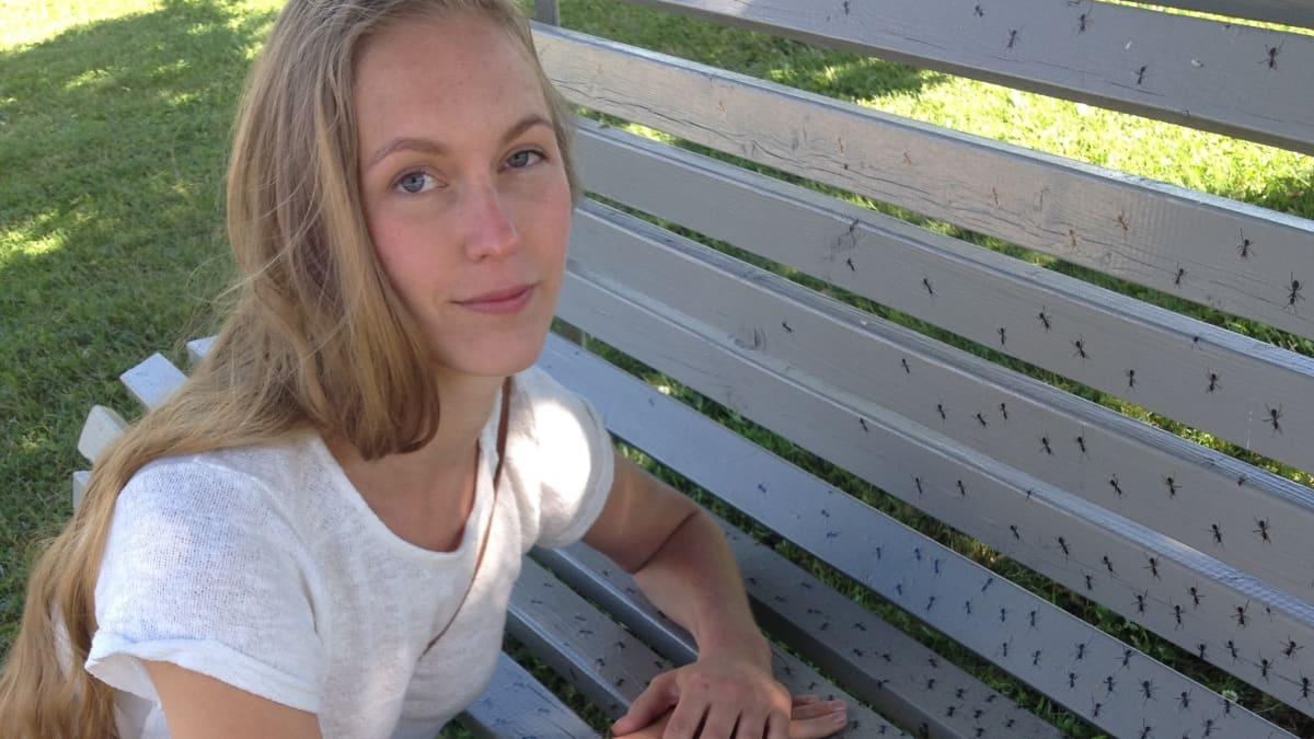 Taiteilija Hanna Ola nojaa muurahaisia kuhisevaan puistonpenkkiin.