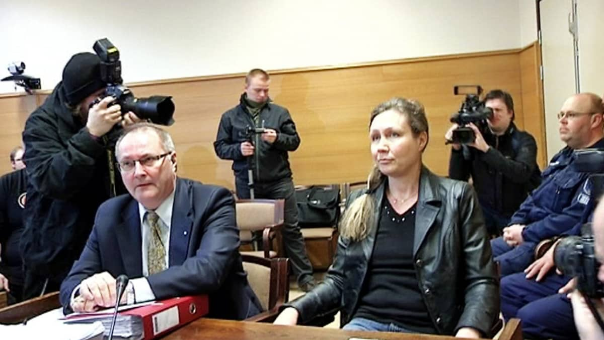 Anneli Auer oikeudenkäynnissä kuvaajien ympäröimänä.