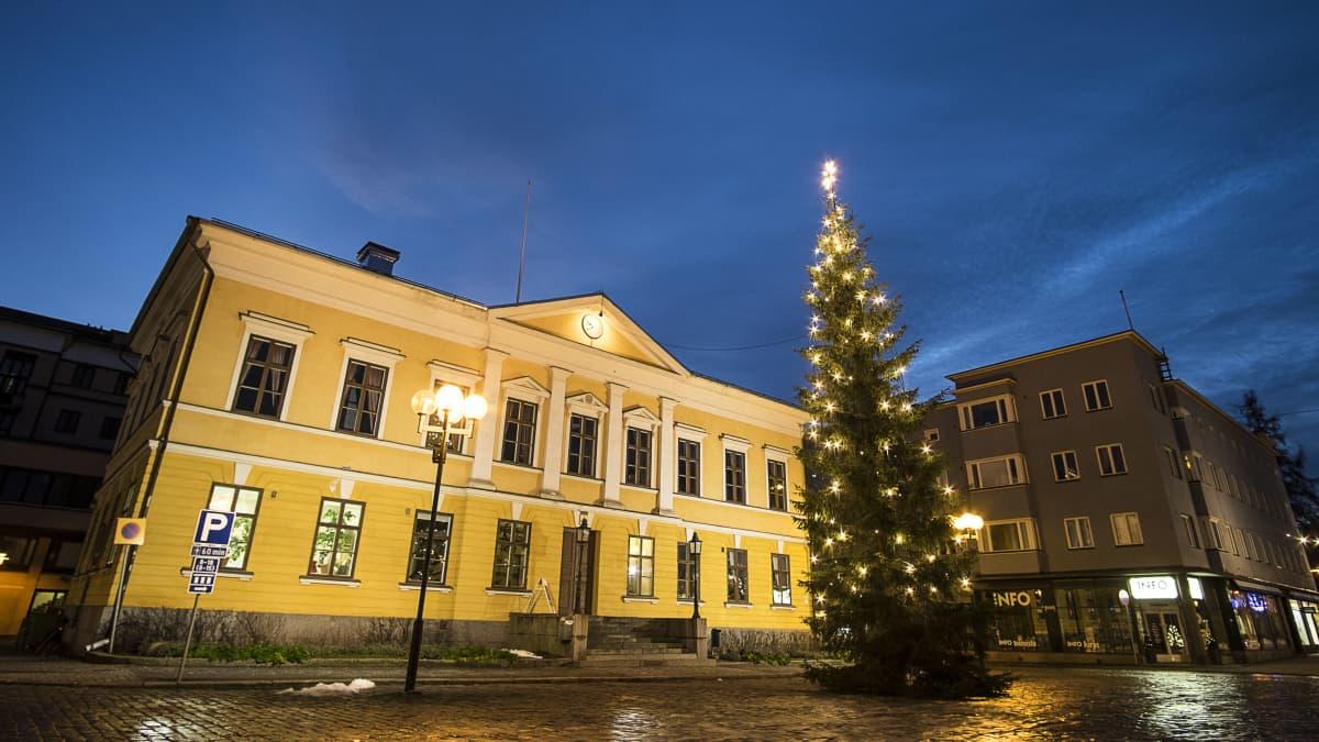 Joulukuusi Kokkolan Raatihuoneen edessä.  Keltainnen rakennus, taustalla tummaa taivasta.