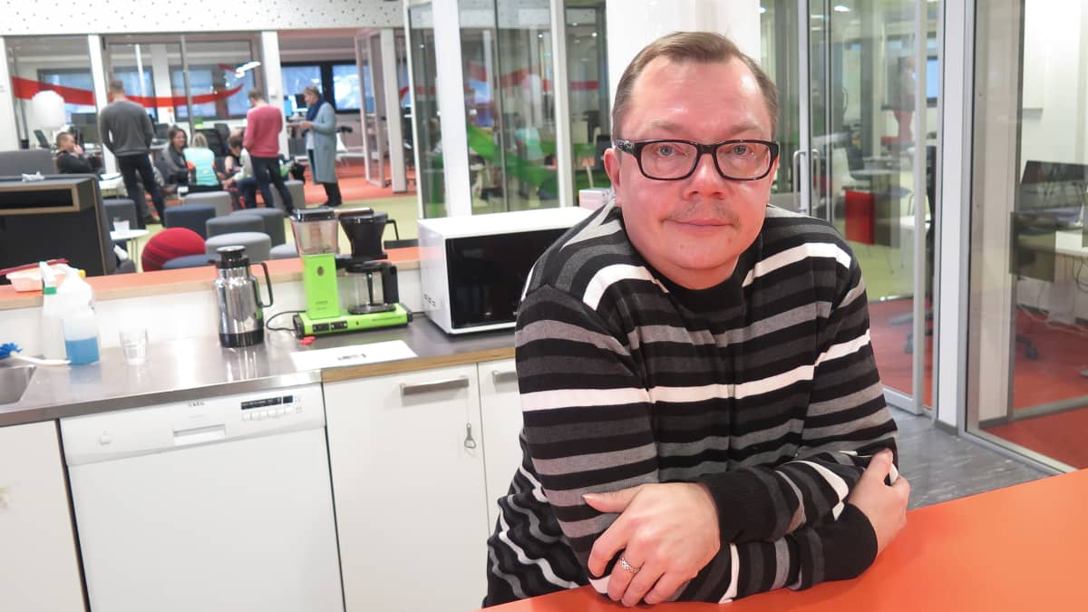 Mies nojaa keittiön pöytään Yle Tampereen toimituksessa