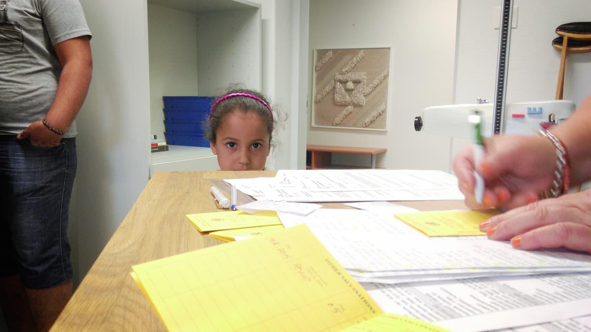 pieni tyttö katsoo pöydän takaa.