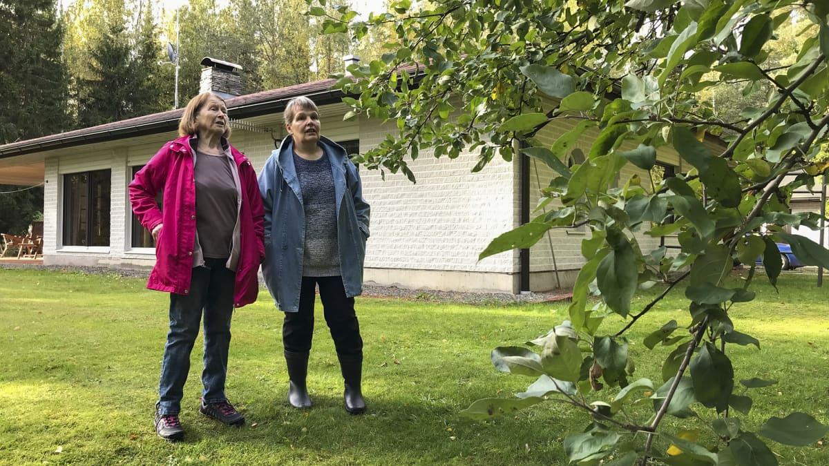 Kaksi naista seisoo puutarhassa.