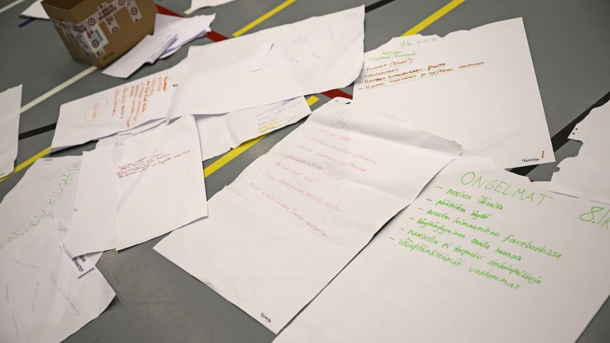 Nuorten kirjoittamia ajatuksia paperilla.