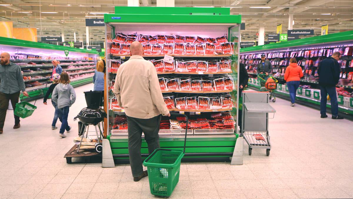 Asiakas katselee makkaroita kaupan kylmähyllyssä