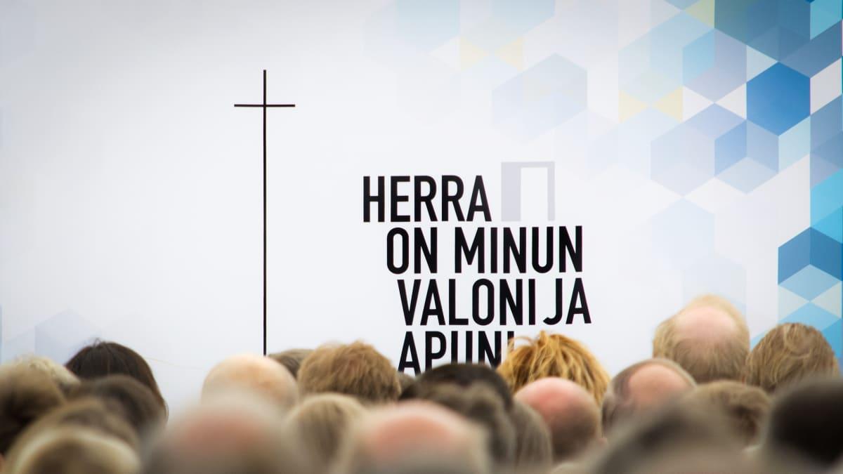 Herra on minun valoni ja apuni -teksti Suviseurojen pääteltassa Vaasassa. Etualalla messuihmisiä takaa kuvattuna.