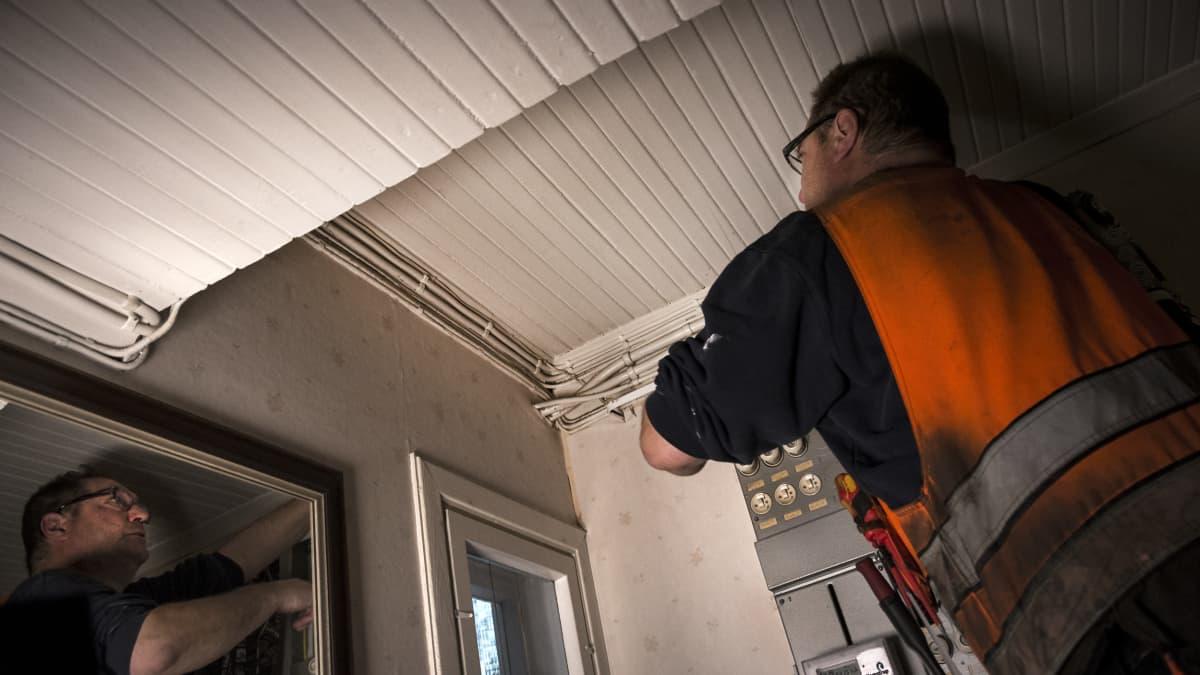 Sähköinsinööri tarkistaa vanhan rintamamiestalon sähköjohtoja.