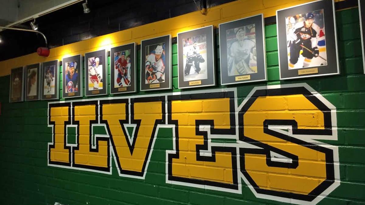 Pelaajien valokuvia käytävän seinällä Hakametsän jäähallissa.