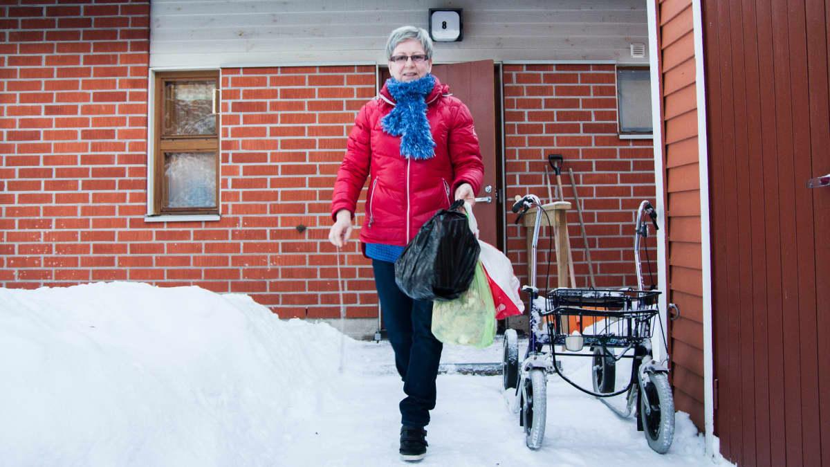 Kotihoitaja Paula Keränen vie asiakkaan roskia Hyrynsalmella.