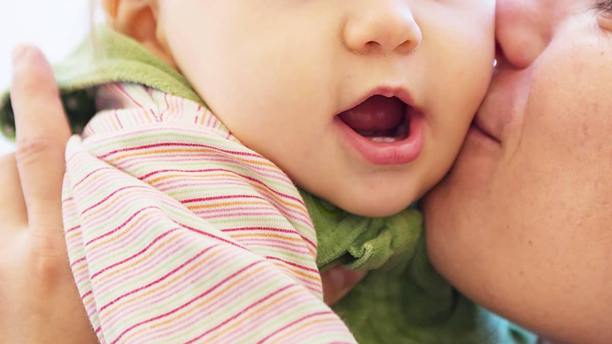 Äiti antaa suukon lapselle.