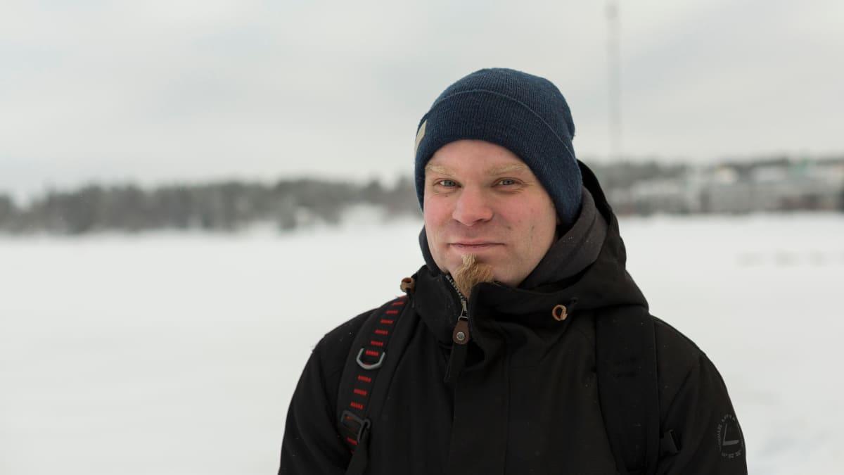 Mies seisoo lumisessa maisemassa joen rannassa.